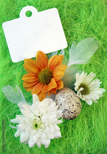Tuinposter Natuur Easter still-life with flowers, eggs, feathers on a green sisal fiber with a sign