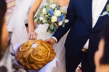 The bride and groom break a piece of wedding bread