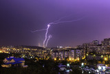Lightning hitting the bridge during a purple sunset in the city