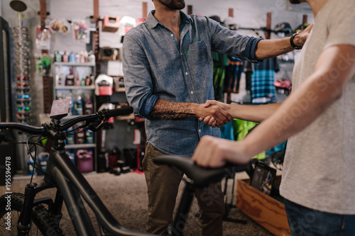 Sports shop owner selling bicycle to customer