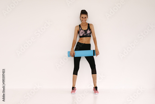 Plakat Woman in fitness studio with a yoga mat