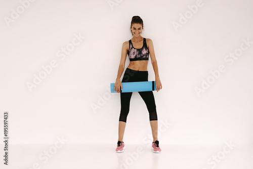 Fototapeta Woman in fitness studio with a yoga mat