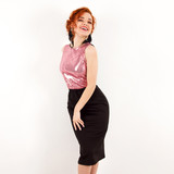 young girl with red hair in a pink shiny blouse and black skirt standing and smiling on a white wall background