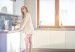 Young woman standing in kitchen.