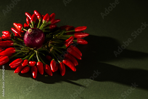 Fotobehang Hot chili peppers corona di peperoncini rossi e cipolla su sfondo verde