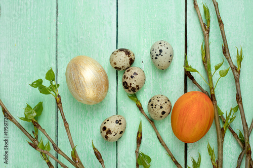 Fotobehang Lelietjes van dalen Easter eggs and branch with leaves on wooden table background. Top view. Copy space for text.