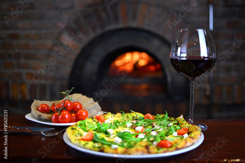 Papiers peints Pizzeria Tasty pizza and glass with red wine in a traditional restaurant with a fire stone stove. Background with a tasty food.