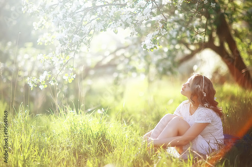 spring girl apple flowers, nature portrait of happy girl with long hair in blooming apple trees, freedom purity concept of happiness - 195649469