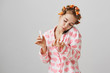 Treat yourself like queen. Portrait of attractive young woman in hair curlers and pyjamas, holding smartphone on shoulder while talking with friend, painting nails, and blowing on it to dry faster