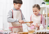 Girl and boy cooking in home kitchen, making the dough for baking, healthy food concept - 195658227
