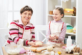 Mother and daughter cooking at home, making the dough for buns - 195658460