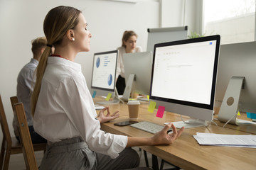 Calm peaceful young businesswoman meditating at office desk with eyes closed, company employee manager practicing yoga at workplace for mental emotional balance, no stress at work relief, side view