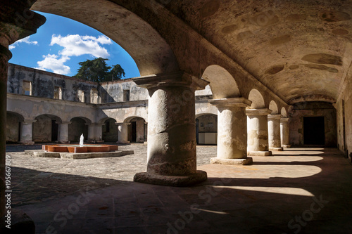 Fotobehang Centraal-Amerika Landen Under the arches of the courtyard with fontain of Capuchins Monastery in Antigua de Guatemala, Guatemala