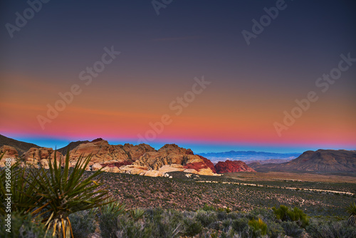 Plexiglas Las Vegas sun setting over redrock canyon rocks with las vegas in background