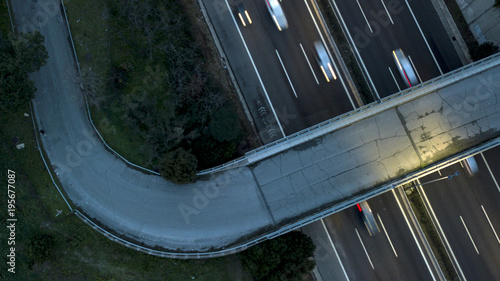 Fotobehang Nacht snelweg Aerial night view of an overhead road and bridge crossing an Italian highway. On the road, many cars drive at high speed with the headlights on.