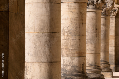 Poster Stenen Colonnade - row of old rough stone corinthian columns, with decorative tops - receding perspective