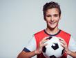smiling teen boy in sportswear holding soccer ball