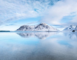 Mountain ridge and reflection on the seashore. Natural landscape in the Norway