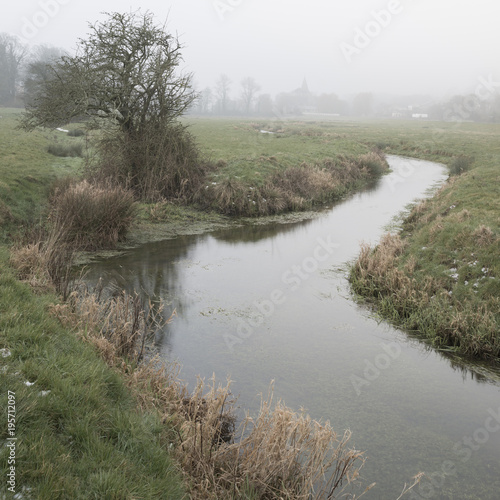 Deurstickers Wit Cold misty Winter landscape over stream in English countryside