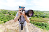 A young man with a camera shoots nature against the background of rocks and sky - 195717678