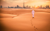 Arabic man with traditional emirates clothes walking in the desert - 195721223