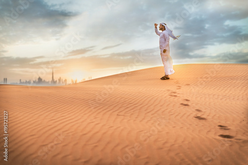 Foto op Aluminium Dubai Arabic man with traditional emirates clothes walking in the desert