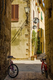 Old street in Pienza with two bicycles; Italy