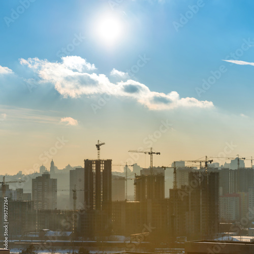Construction site with industrial cranes in city at sunset