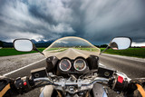 Biker on a motorcycle hurtling down the road in a lightning storm - Forggensee and Schwangau, Germany Bavaria - 195742805