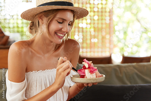 Photo of cheerful young woman in straw summer hat and white blouse, eats delicious cake in restaurant, being satisfied with good service, has pleasant conversation with someone, laughs joyfully