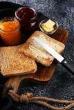 Toast bread with homemade strawberry jam and orange marmalade on rustic table served with butter for breakfast or brunch - 195756274