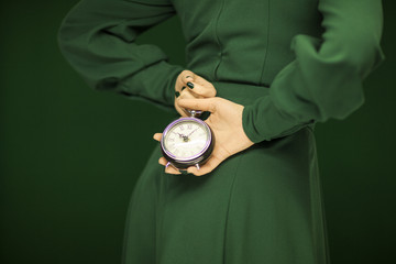beautiful woman figure in green dress with green background holding vintage clock, tone in tone green