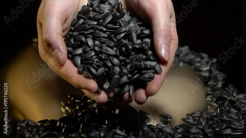 A woman takes a handful of sunflower seeds