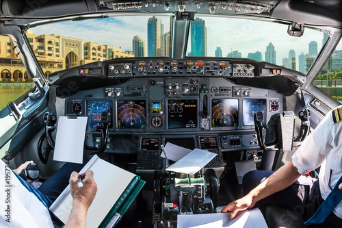 Foto op Aluminium Dubai Airplane cockpit flying on Dubai skyscrapers skyline at sunset, United Arab Emirates, with pilots arms and blank white papers for copy space.