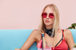 Portrait of pleasant looking pinup girl wears red stylish shades, has serious look, recreats on comfortable blue sofa, enjoys good rest. Blonde fashionable female feeles relaxed at cafeteria.