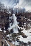 Waterfall Gostilje, Serbia at winter. Snow and ice covered hidden waterfall in the forest in winter.