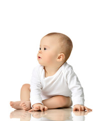 7 month infant child baby  girl toddler sitting in white shirt looking at the corner