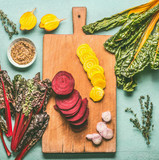 Colorful sliced beetroot on cutting board.  Red and yellow beetroot  with chard  leaves and ingredients on kitchen table background, top view. Vegan or vegetarian clean food concept - 195827257
