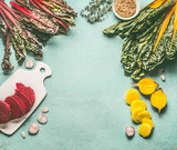 Colorful beetroot cooking preparation with red and yellow sliced beetroot, chard  leaves and ingredients on light blue kitchen table background, top view, frame. Vegan or vegetarian clean food concept - 195827420