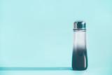 Cosmetic liquid product bottle with essence , toner or cleansing oil on light blue background, front view, copy space. Beauty product concept. Blank label for branding mock-up - 195828435