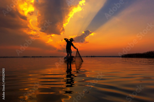 Fotobehang Strand Silhouette fisherman with sunset,Take photo fisherman young woman with sunset
