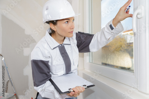 woman measuring the wall with tape measure - 195835287