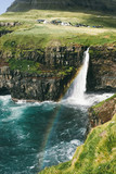 Beautiful huge waterfall dropping at the ocean in Faroe islands, old village, cliffs, rainbow