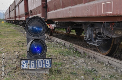 Signaling equipment on railway. A blue traffic light next to the track.