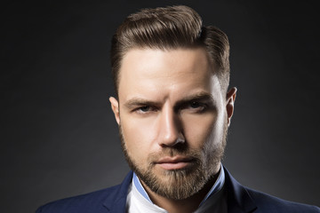 Brunette hair handsome man with beard wearing suit and shirt over dark background