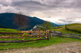 lovely rural landscape in Carpathians. wooden fence along the road on a cloudy day in mountains - 195857036