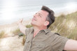 handsome man outdoors on the wild beach arms outstretched enjoys happiness concept of freedom