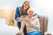 Close people. Positive emotional elderly woman sitting in a soft comfortable armchair while her kind attentive loving granddaughter standing behind her back and softly hugging her