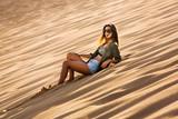 Young girl lying on a sand dune - 195864694