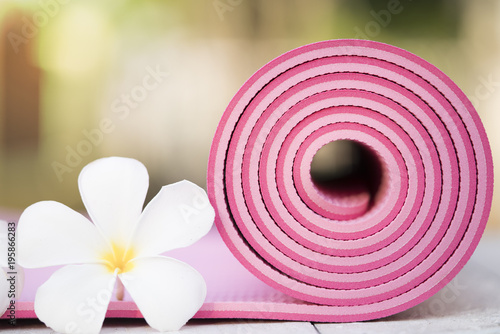 close up of pink yoga mat and flower on the table, sport and healthy concept